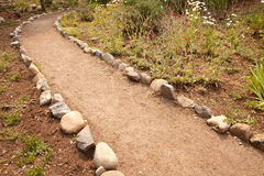 River Rock Lined Dirt Garden Path Stock Photo