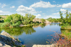 River with rock outcrops and trees on its banks Royalty Free Stock Images