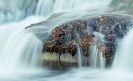 River rock under splashing water. A strong, firm and solid rock resists the strong water current in a fast-flowing river in northeastern Catalonia stock photography