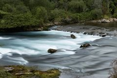 River with rocks and milky water. A cascading river with green foliage, river rocks, and milky water royalty free stock photos