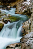 River rocks in smooth satin water flow of waterfall in wintertime Royalty Free Stock Photos