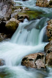 River rocks in smooth satin water flow of waterfall in wintertime Royalty Free Stock Images
