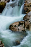 River rocks in smooth satin water flow of waterfall in wintertime Stock Photography
