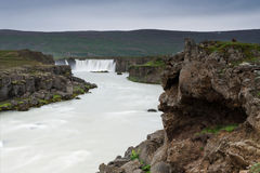 River among rocky cliffs with a waterfall in a distance, Iceland Royalty Free Stock Photos