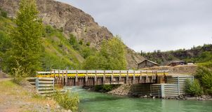 A river running through a canyon in northern canada. A bridge leading to the town at telegraph creek Stock Photography