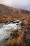 River running from hills into foreground. River flowing through glen, Glencoe, Argyll, Scottish Highlands. Clouds gather ominously on the hillside Royalty Free Stock Photos