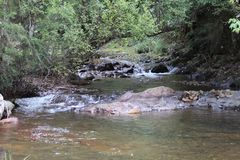 River Running Over Rocks in High Country. The river is running over rocks and stones from high in the hills.  The river runs for thousands of miles of kilometres Stock Photo