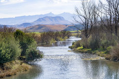 A river runs through the foothills of the Drakensberg Mountain Range at Underberg in South Africa. Stock Photos