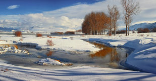 The river runs through the frozen field. Covered with snow , blue sky in the background Royalty Free Stock Images