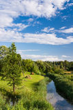 River in rural area. Small river with curves and hayfield under blue sky Stock Photos