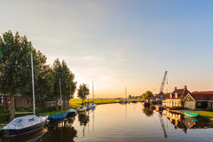 River with sailing boats in the Dutch province of Friesland. During sunset Stock Photos