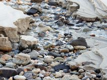 Stones, sand and water. A river in the sand on the beach.The sea stones background. Pebble stones background texture closeup of stones and water Royalty Free Stock Image