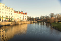 River with scandinavian building on left side and right side is park. Stock Photos