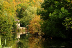 River scene. Beautiful rural river Autumn landscape surrounded with green trees, reflection and small building and boat in distance Royalty Free Stock Images