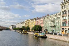 Bright coloured buildings along the river in Saint Petersburg, Russia. River scene showing brightly coloured buildings on one side of the water. Boats are near royalty free stock images