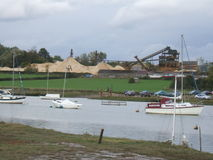 River Scenery with Construction. The scene of a river with boats and the background of tents and construction Stock Photo