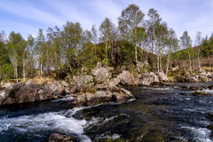 River in Scotland in the woods, with a blue  skye. Little falls in a river in Scotland in a wood Royalty Free Stock Photos