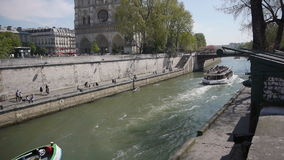 River Seine at Ile de la Cite. Paris, France. The shot is taken from a bridge over the Seine. The famous river Seine at the foreground with some tourist boats stock video footage