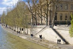 River Seine, Paris, France. Tourists stroll along the Right Bank of the Seine in Spring sunshine Royalty Free Stock Photo