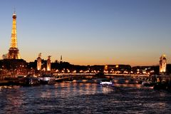 River Seine Paris by night with Alexandre III bridge and Eiffel Tower illuminated france. Paris by night cityscape panorama of River Seine at Paris with royalty free stock photo