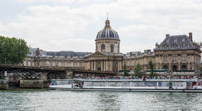 River Seine in Paris with tourist boat cruise. Tourist boat cruise on River Seine near Pont de Arts bridge and historic buildings Royalty Free Stock Photo