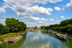 River, ships and bridge in Paris, France on natural background. Green water and trees on cloudy blue sky. Landmark and tourist destination. Summer vacation and Stock Images