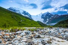 From the river shore, covered with stones, opens view on fantastic glacier and steep rocky mountains with green meadows. Royalty Free Stock Image