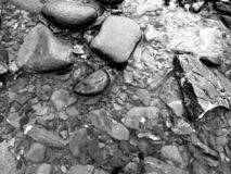 River shore rocks in black and white royalty free stock photos