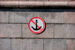 River sign mooring prohibited. Round river mooring prohibited sign on the granite facing of the canal bank Royalty Free Stock Image
