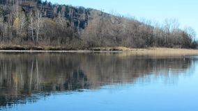 The river with a slow current on the background of the mountains in early spring in the daytime stock footage