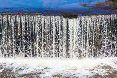 River Small Weir Water Movement. River water pouring over small wall weir with motion movement Stock Images