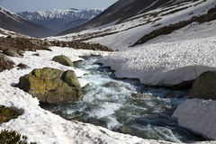 River with snow bridges in spring mountains at sun day Royalty Free Stock Image