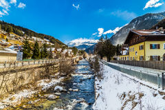 River through snowy alpine village. River passing through snowy alpine village in Italy illuminated by sun with mountains in the background Stock Photos