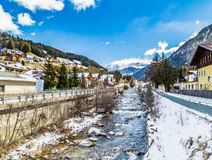 River through snowy alpine village. River passing through snowy alpine village in Italy illuminated by sun with mountains in the background Stock Image