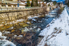 River through snowy alpine village. River passing through snowy alpine village in Italy illuminated by sun with mountains in the background Royalty Free Stock Photography