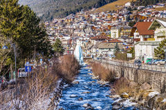 River through snowy alpine village. River passing through snowy alpine village in Italy illuminated by sun with mountains in the background Stock Photography