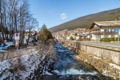 River through snowy alpine village. River passing through snowy alpine village in Italy illuminated by sun with mountains in the background Royalty Free Stock Images