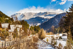 River through snowy alpine village. River passing through snowy alpine village in Italy illuminated by sun with mountains in the background Royalty Free Stock Image