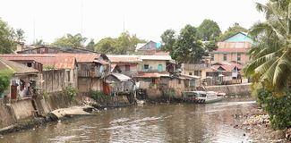 River in Sorong. River with poor houses on bank in Sorong (Papua Barat, Indonesia Stock Photo
