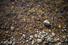 River stone beach, natural color river stone under clear water. Outdoor day light stock images