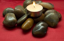 River stones, pebbles and lighted candle. Pile of stones on a red background Royalty Free Stock Images