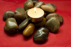 River stones, pebbles and lighted candle. Pile of stones on a red background Royalty Free Stock Image
