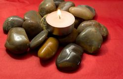 River stones, pebbles and lighted candle. Pile of stones on a red background Stock Photos