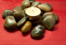 River stones, pebbles and lighted candle. Pile of stones on a red background Stock Photo