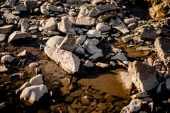 River stones shot in warw evening light. River stones, Pebble river banks.great for gaming background, shot in warm evening light royalty free stock photography