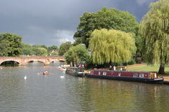 River at stratford on avon england. Bridge over river at stratford on avon England cloudy skies sunlit river and trees moored barges boaters boating swans Royalty Free Stock Photography
