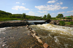 River with strong current flows under bridge Royalty Free Stock Photo
