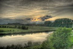 River in the sunset. HDR modified view of river, riverbanks, meadow in the sunset Stock Photos