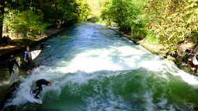 River surfing the Eisbachwelle downtown Munich stock video