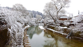 River Surrounded with Snow. Miyagawa river that runs through Hida Takayama old town covered with snow in winter Royalty Free Stock Photo